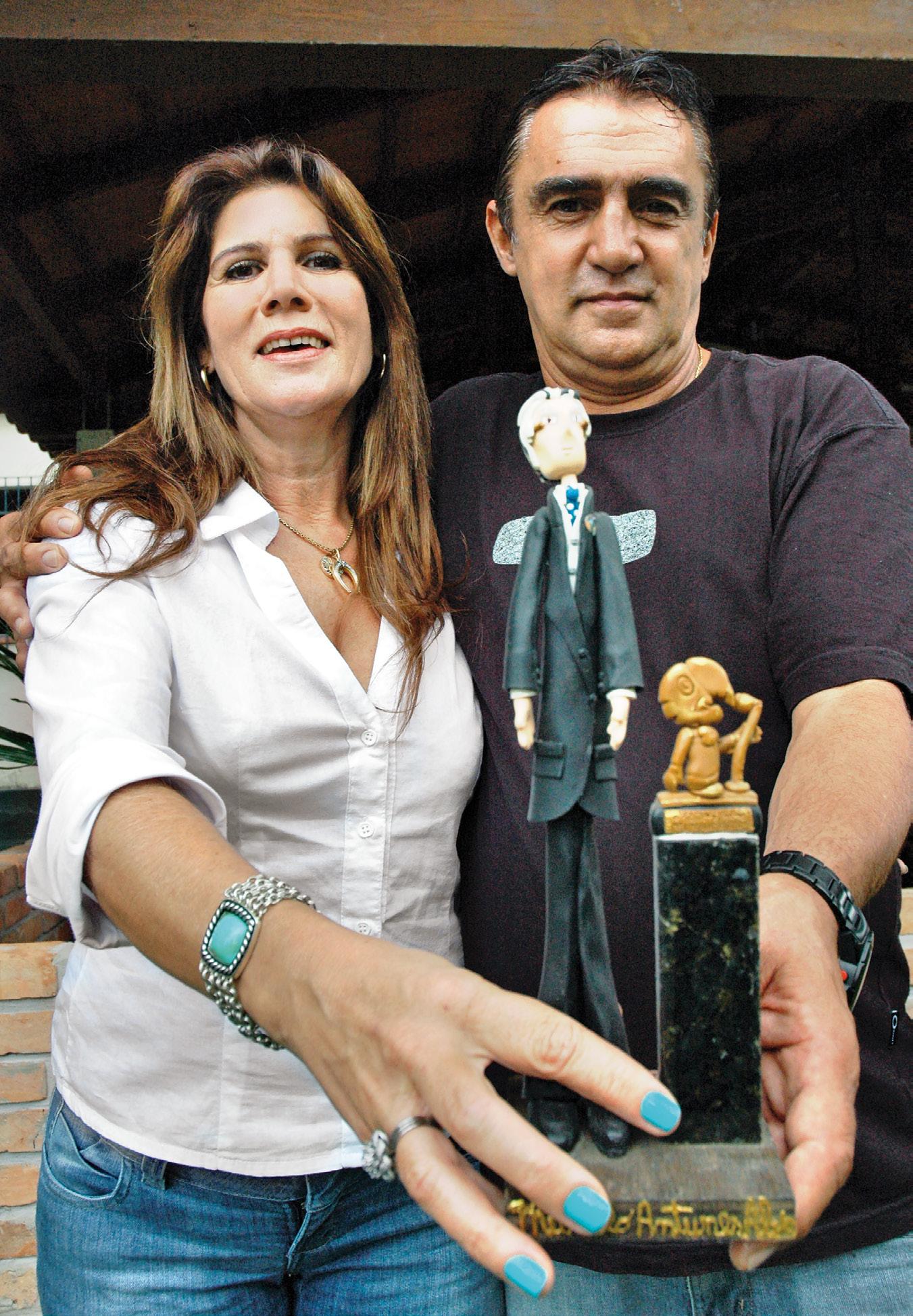 Nora e filho mostram troféu Roquette Pinto com escultura de Murillo